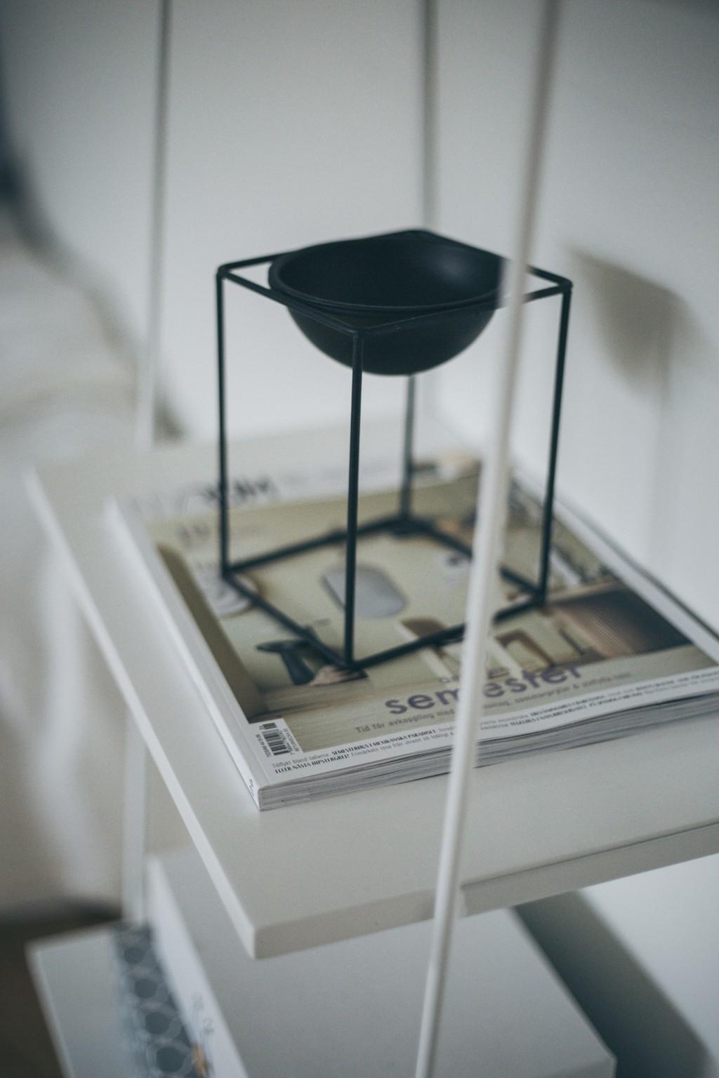 vitt hyllplan med inredningstidning och svart skål