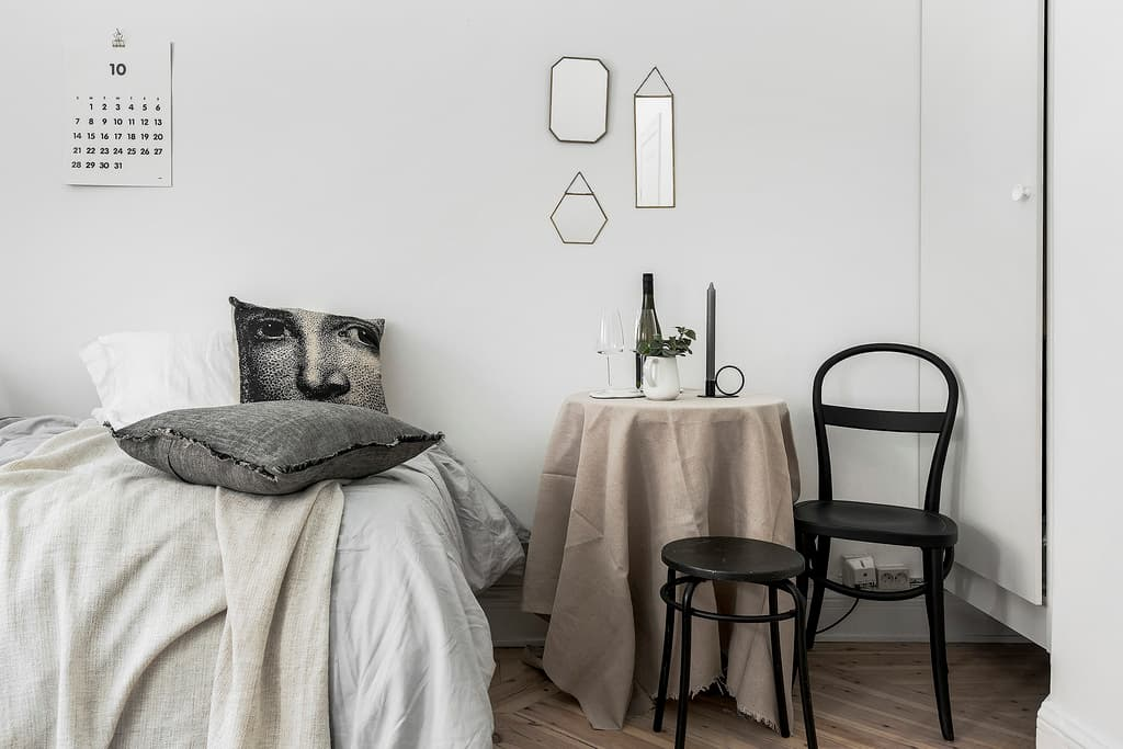 bäddad säng bredvid ett dukat bord med stol och pall