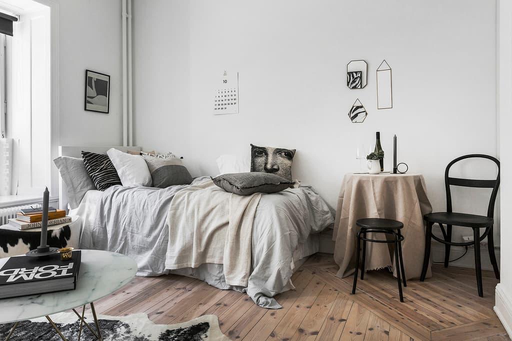 bäddad säng med ljusa grå och beige färger