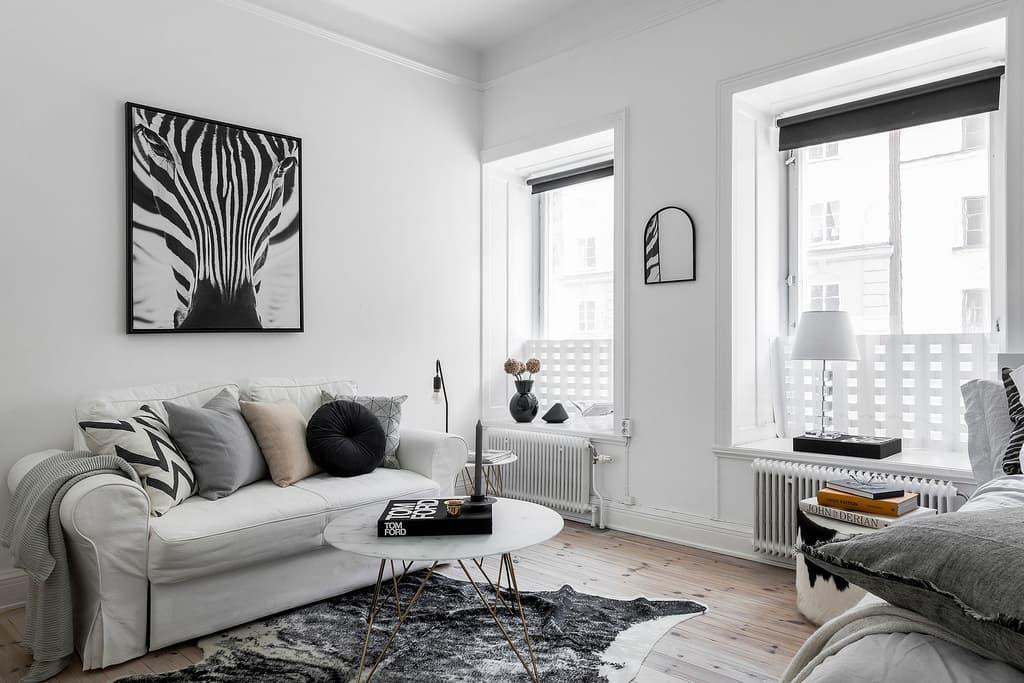 vardagsrum med trägolv, ljusa väggar och ljus inredning