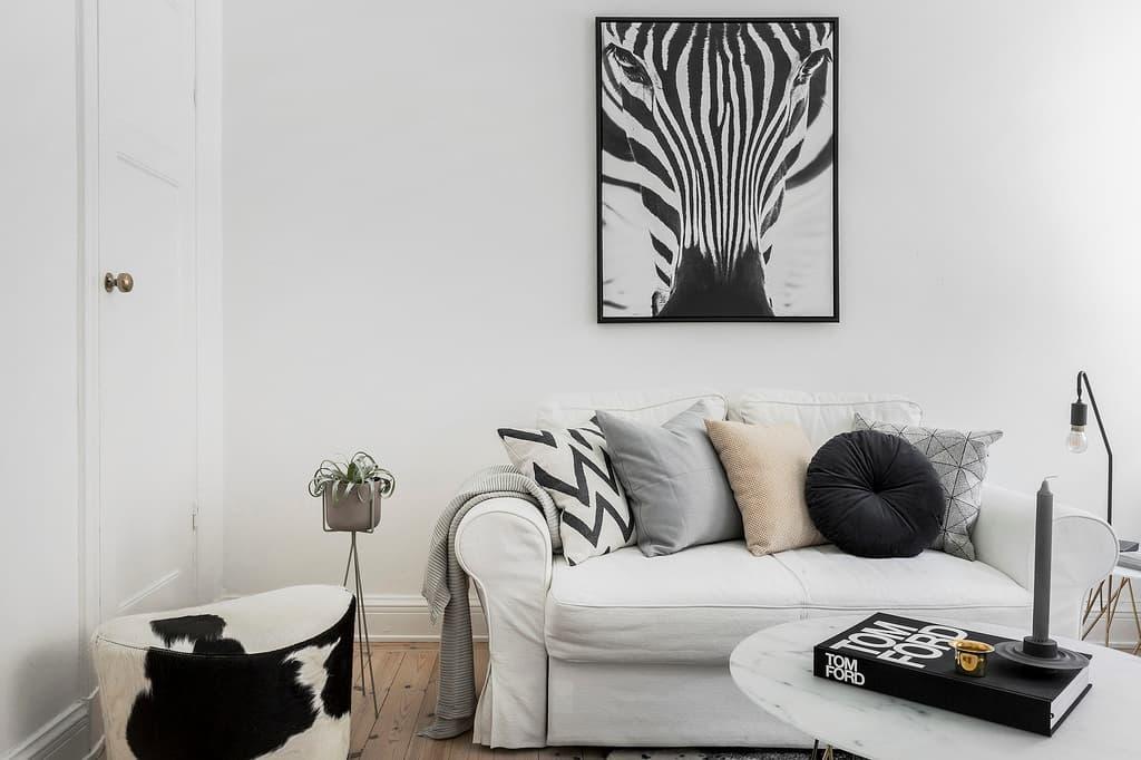 vit soffa med kuddar och en tavla med ett zebra ansikte bakom