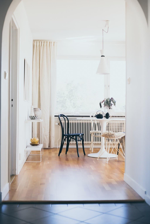 hall in mot vardagsrum med bord och stolar runt