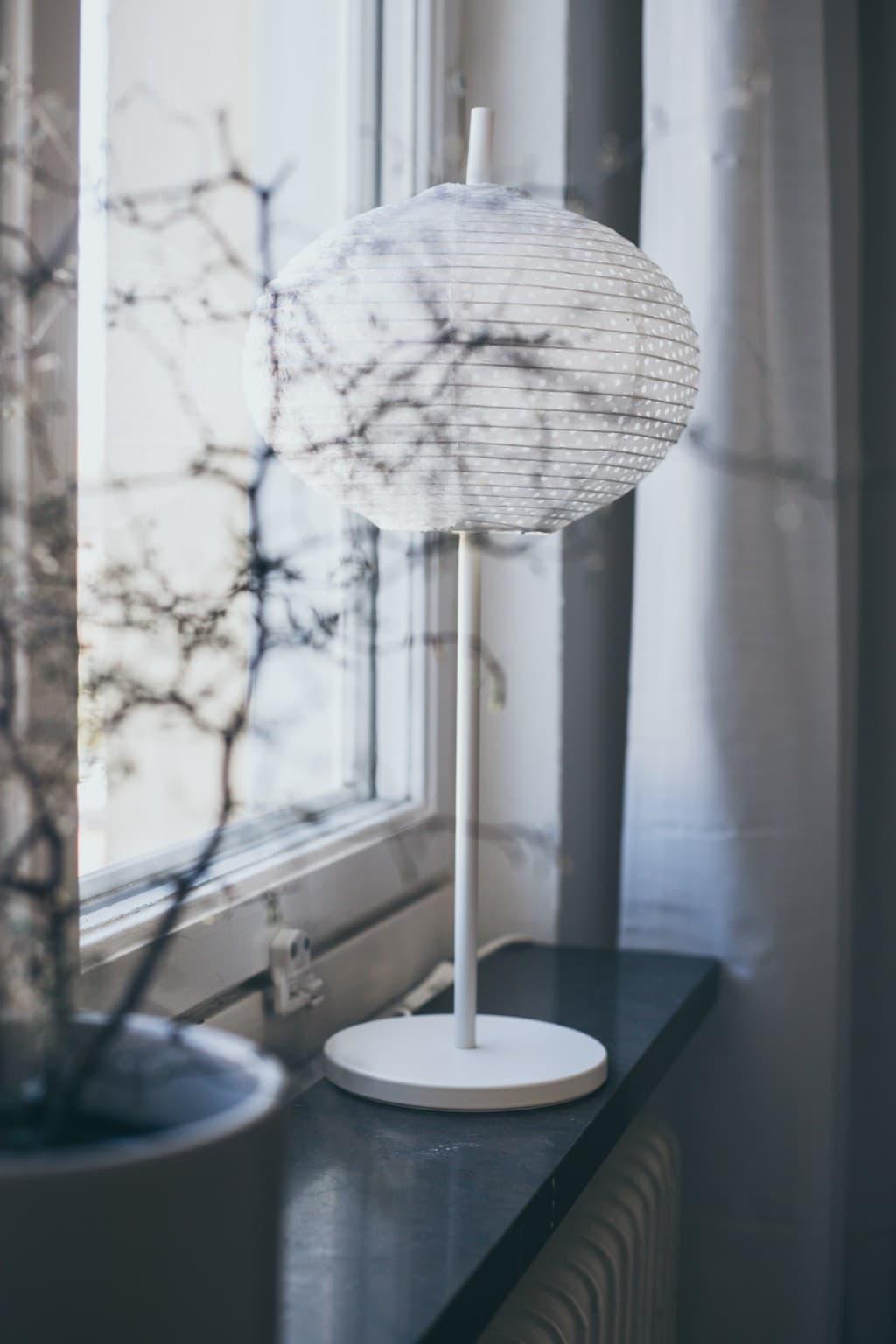 svart fönsterbräda med kruka och lampa