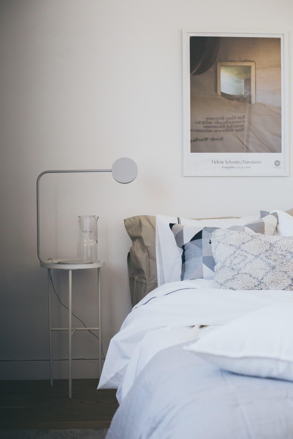 bäddad säng med kuddar, sängbord och bordslampa bredvid