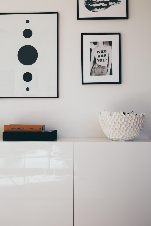 vitt skåp med skål och tavlor ovanför
