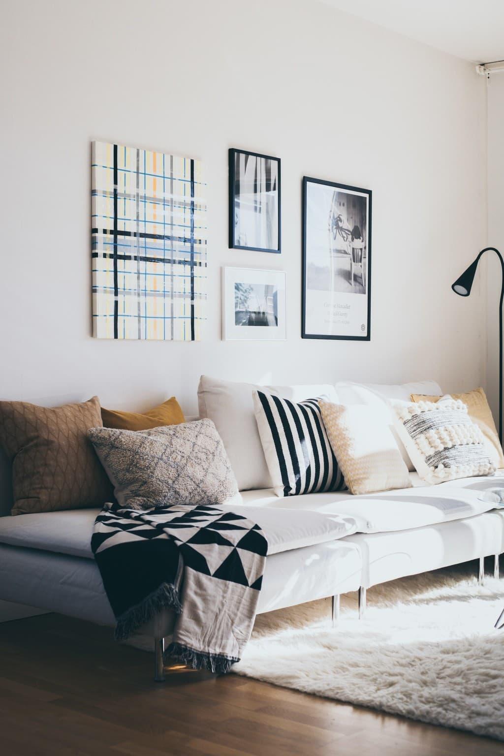 vit soffa med massa kuddar och tavlor ovanför