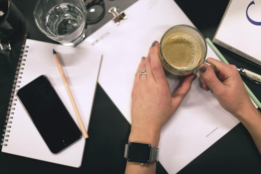 närbild på block, penna, telefon och två händer hållandes en kaffekopp