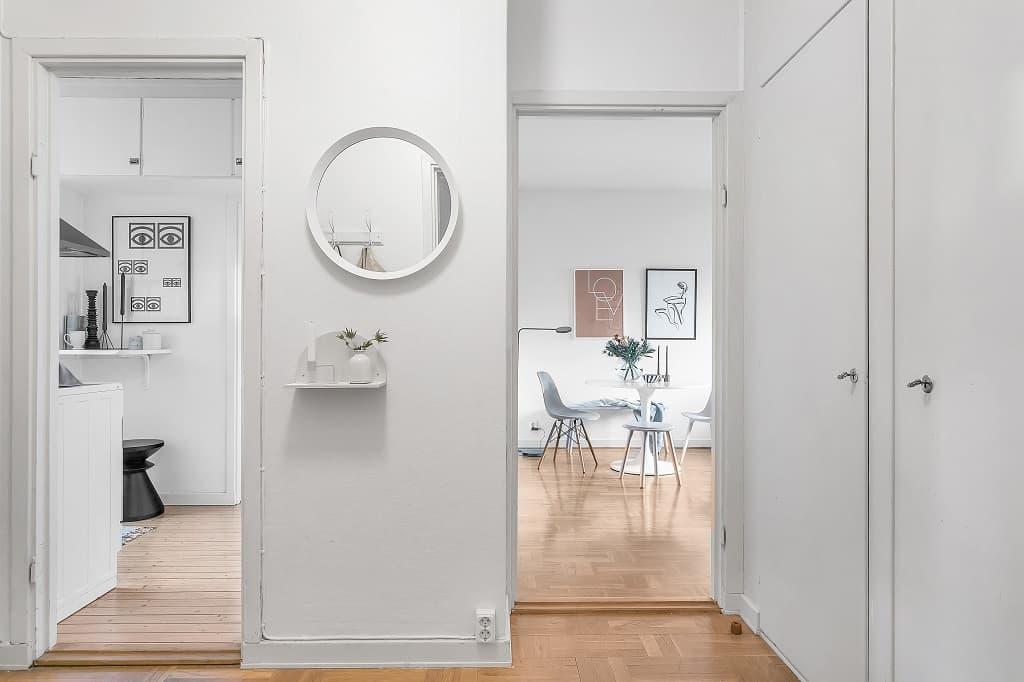 hall med dörröppningar in i kök och vardagsrum